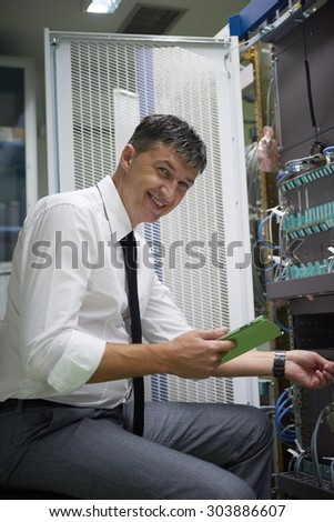 network engineer working in  server room, corporate business man working on tablet computer - stock photo
