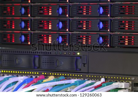 Network hub and server rack storage with connection cables and red lights - stock photo