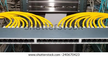 Network Patch Panel in a datacenter with networkcables - stock photo