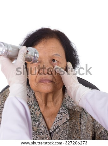 Neurologist testing reflexes of the eye of young woman on white background - stock photo