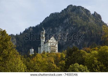 neuschannstein castle on a hill in bavaria with autumn foliage - stock photo