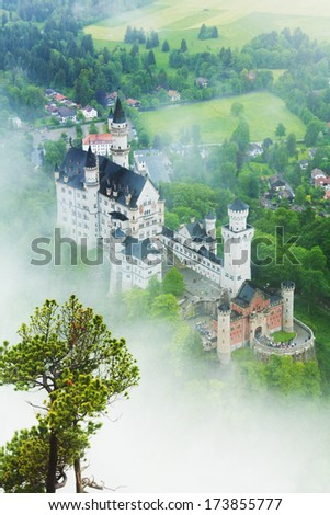 Neuschwanstein in the morning mist of fog and mist, view from above - stock photo