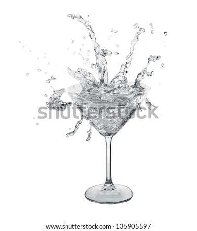 Neutral color water slashes in martini glass. Isolated on white. - stock photo