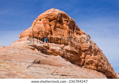 "Nevada State Park ""Valley of Fire"". A child comes out of the cave in the red rock - stock photo"