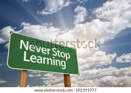 Never Stop Learning Green Road Sign with Dramatic Clouds and Sky. - stock photo