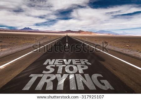 Never Stop Trying written on desert road - stock photo