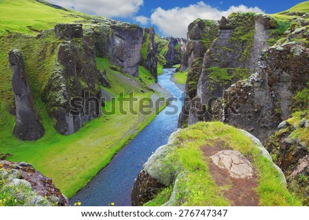 Neverland Iceland. The picturesque canyon Fjadrargljufur, green cliffs and blue water of the river - stock photo