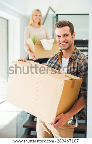 New apartment for two. Cheerful young couple holding cardboard boxes while standing in their new house - stock photo