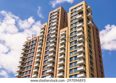 New block of modern apartments with balconies and blue sky in the background - stock photo