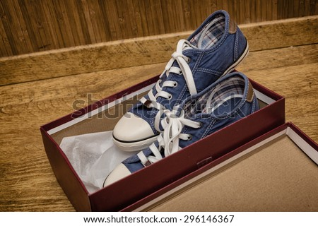 New blue sneakers in a cardboard box on a wooden floor - stock photo
