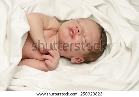 New born baby boy smiling in his sleep. Small baby happy making cute faces during his nap. - stock photo