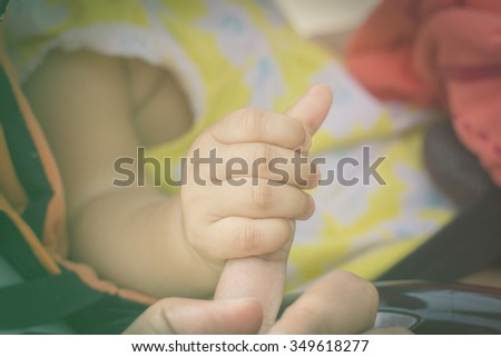 New born baby hand with mother hand in vintage tone style - stock photo