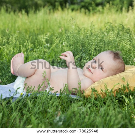 New born baby lay on yellow pillow in park - stock photo