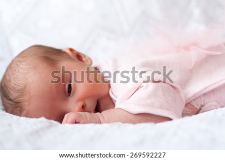 new born baby lying on texture blanket, light pink dress with bow-knot on back - stock photo