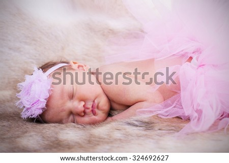 New born baby wearing a pink head band and tutu.  - stock photo