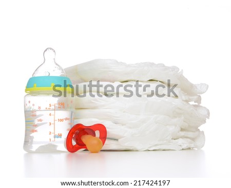 New born child stack of diapers nipple soother and baby feeding bottle with water on a white background - stock photo