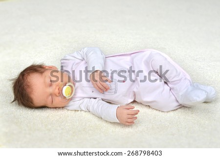 New born infant child baby girl sleeping on a warm blanket - stock photo
