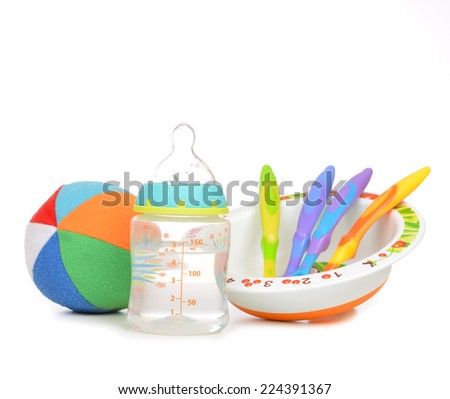 New born infant child composition baby spoons in plate feeding milk bottle with water and ball on a white background - stock photo