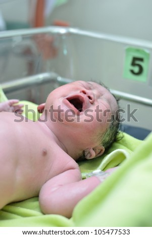 New born infant from cesarean section in operating theater. - stock photo