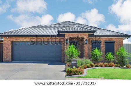 new brick house with green lawn and plants - stock photo