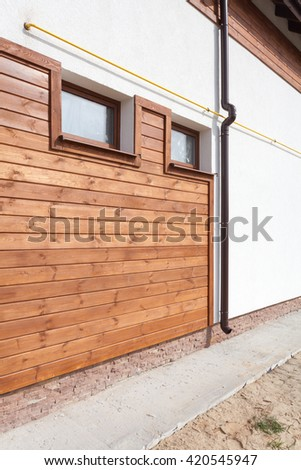 New brown copper gutter in house with white wall and wooden planks - stock photo