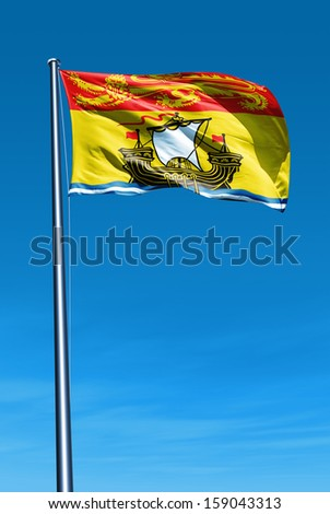 New Brunswick (Canada) flag waving on the wind - stock photo