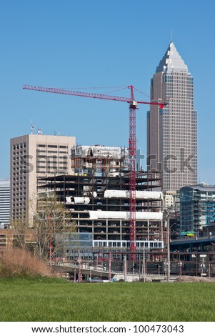 New building construction site with a skyscraper in the background and a cloudless blue sky overhead - stock photo