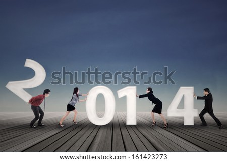 New business arrangement concept with bussinesspeople arrange new year of 2014 - stock photo