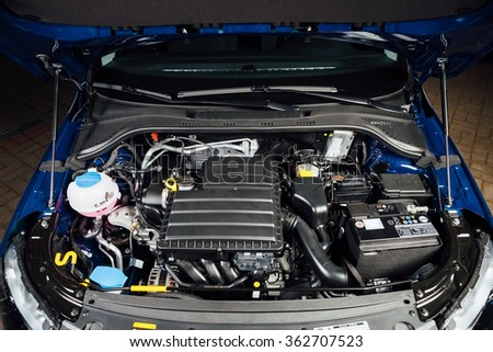 new car engine and parts under hood - stock photo