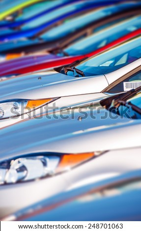 New Cars Stock in Row. Modern Compact Cars Dealership Parking Lot Closeup. - stock photo