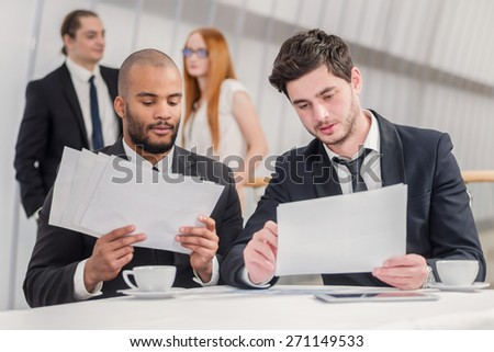 New challenges. Two successful businessman sitting at a desk holding papers in his hands and looking into the camera while their colleagues standing in the background and shake hands - stock photo