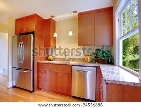 New cherry kitchen with grey granite and stainless steal appliances. - stock photo
