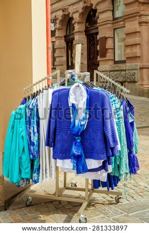 New collection of clothes hanging on a rail outside - stock photo