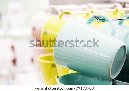 New colored mugs cups on a shop shelf - stock photo