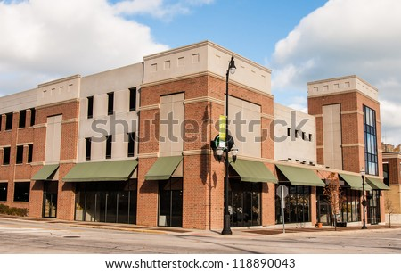 New Commercial, Retail and Office Space available for sale or lease in generic red brick office building with awning - stock photo