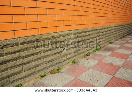 New construction waterproofing basement walls from outside with detail of a pavement to walk. Foundation ventilation. - stock photo