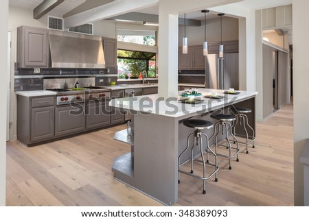 New decorated grey Kitchen in luxury home with marble counter top, kitchen island, modern black chrome bar stools and wooden floor. - stock photo