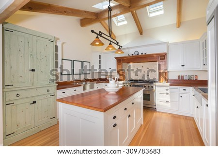 New decorated white Kitchen in luxury home with amazing wooden counter top, kitchen island and wooden floor. - stock photo