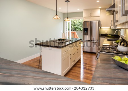 New decorated white Kitchen in luxury home with black granite counter top and wooden floor. - stock photo