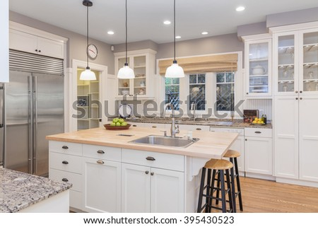 New decorated white large Kitchen in luxury home with new wooden counter top, kitchen island, new stainless steel appliances, pantry and and white build ins.  - stock photo