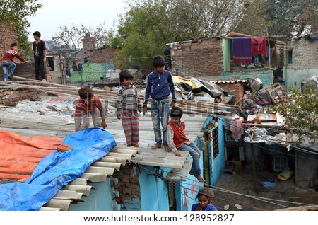 NEW DELHI,INDIA-FEBRUARY 4:children not unidentified play on the rooftops of the l slum in New Delhi.50% of the population of New Delhi is thought to live in slums,on February 4,2013 in New Delhi - stock photo