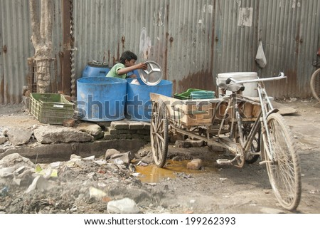 NEW DELHI, INDIA - MARCH 10: Unidentified Indian boy washes dishes on his own tricycle on March 10, 2014 in Delhi, India. Street dishwashers in demand among Indian fast-food restaurants.  - stock photo