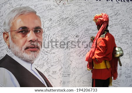 NEW DELHI-MAY 16:  A musician  writing a message on a message board to write best wishes for Mr. Modi after wining the Indian National election on May 16, 2014 in New Delhi , India. - stock photo