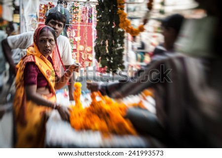 NEW DELHI -  NOVEMBER 16: Man threading colourful flower garlands on November 16, 2013 in Delhi, India. These flowers are offered to the gods in the temples  - stock photo