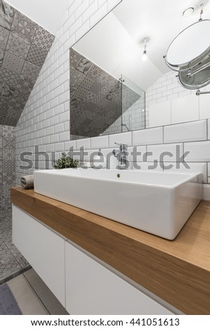 New design bathroom with white brick effect tiles, big basin and mirror - stock photo