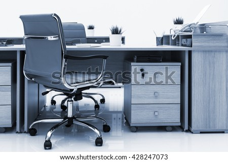 new desks and armchairs on a white wall - stock photo