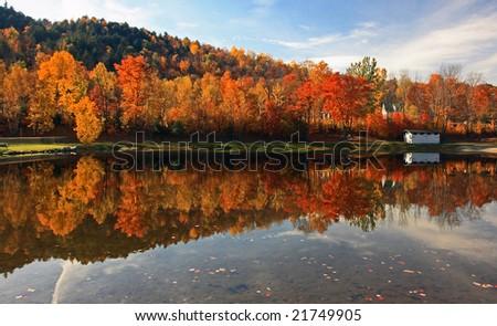 New England foliage along pond with reflection - stock photo