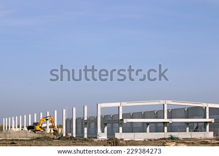 new factory construction site with excavator - stock photo