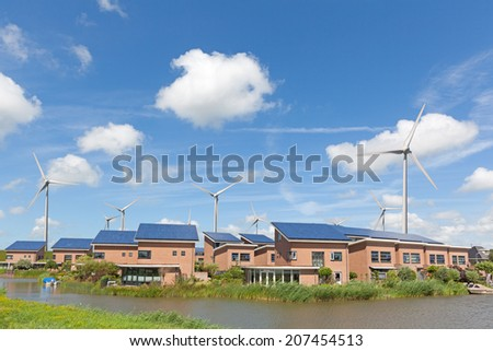 New family homes with solar panels and wind turbines - stock photo