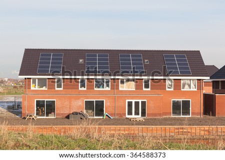 New family homes with solar panels on the roof - stock photo
